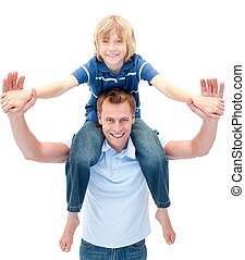 Charming father giving his son piggyback ride against a...
