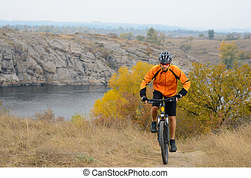 Cyclist Riding Bike on the Beautiful Autumn Mountain Trail...