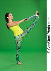 Woman doing pilates with ring on green background