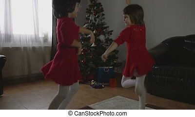 Twin Girls dancing Cristmas morning - Young beautiful twin...