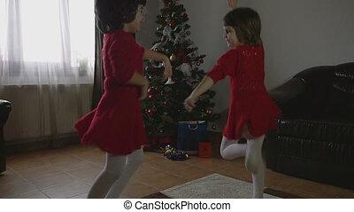 Twin Girls dancing Cristmas morning - Young beautiful twin...