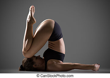 Variation of Knee to Ear Yoga Pose - Attractive young fit...