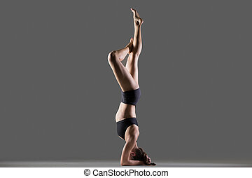 Headstand Exercise - Beautiful young fit woman doing sport...