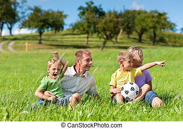 Family with children and football on a meadow - Family with...