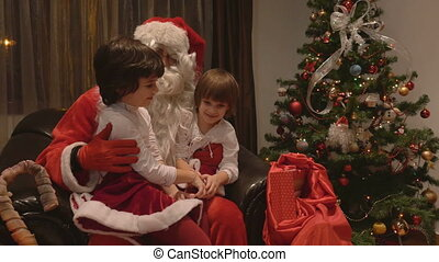 Girls sitting in Santa Claus Lap - Young beautiful twin...