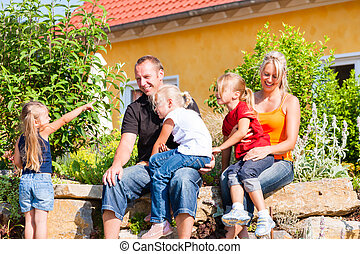 Family in front of home or house