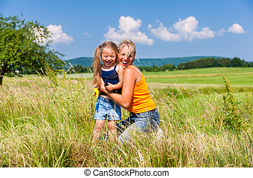 Mother and Daughter in summer on meadow