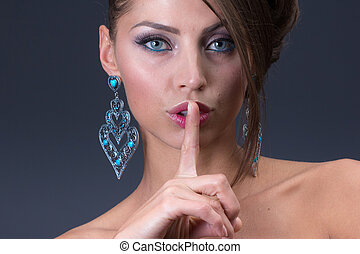 keep silence signal from Woman wearing shiny blue earring