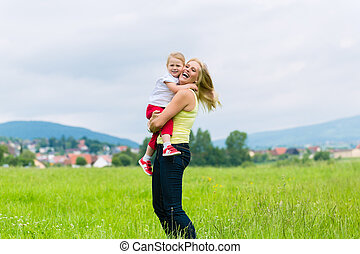 Mother and daughter on a summer meadow