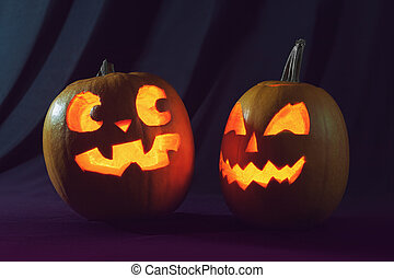 Two Halloween pumpkins scaring each other