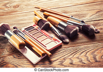 Brushes with cosmetics scattered chaotically on wooden...