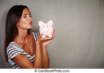 Charismatic young woman kissing a piggy bank