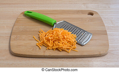 Cheddar cheese with grater on wood cutting board