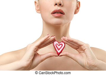 Young woman showing heart shaped candy.