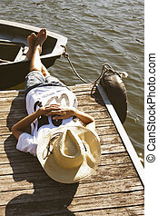 young man sleeping on the pier, vacation