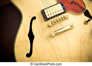 Guitar body detail with sound hole and pickup on wooden...