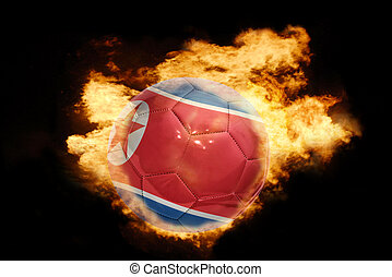 football ball with the flag of north korea on fire -...