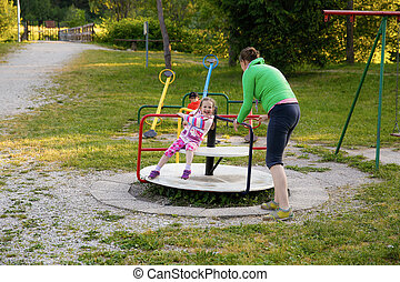 Little girl and her mother on a playground being happy,...
