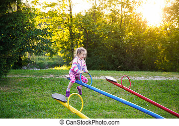 Happy little girl playing, going up ad down on a seesaw on a...