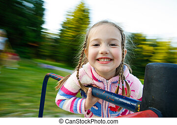 Little girl smiling on a moving merry-go-round - Little girl...