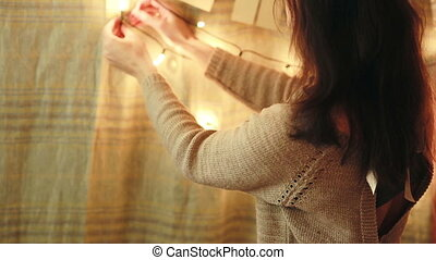 Women decorates the house. light garland and flags - young...