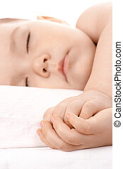 Sleeping little child, clasping his hands together. Shallow...