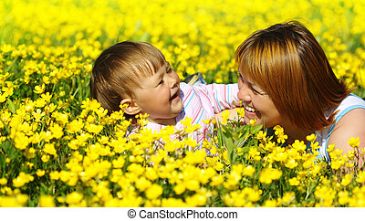 Mother and her child play on meadow
