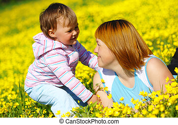 Mother and child play on meadow