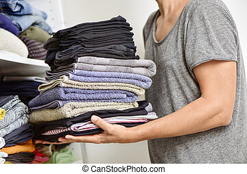 young man with a pile of folded clothes - closeup of a young...