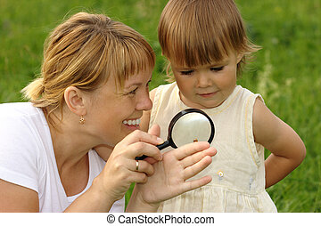 Child with mother looking at snail