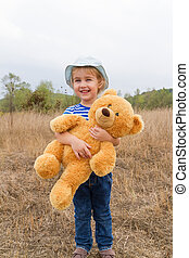 Cute little girl hugging a big Teddy bear - Cute little girl...