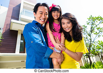 Asian family with child standing in front of home