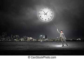 Turn back time - Young businessman trying to turn back time...