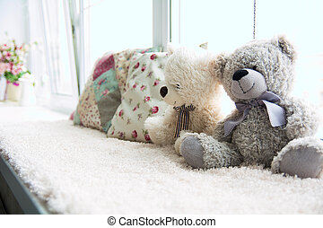 Two teddy bears and two pillows on a light windowsill....