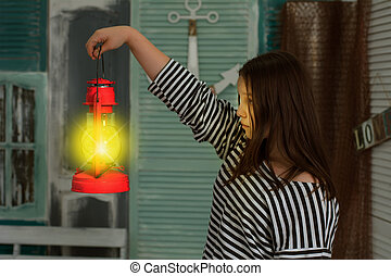 Girl with a lighted kerosene lamp at night in a vintage room...