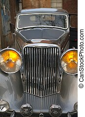 Car vintage, old Jaguar in silver color, yellow headlights
