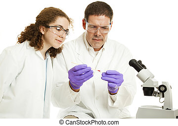 Medical Laboratory - Intern watches as a scientist analysis...