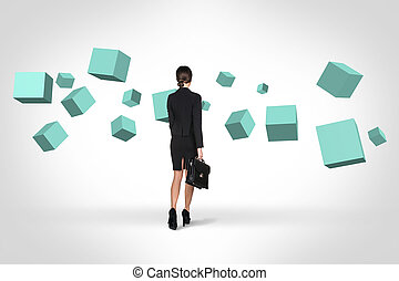 Business woman looking at turquoise cubes suspended in the...