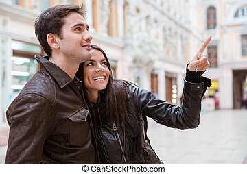 Woman pointing finger on something to her boyfriend -...