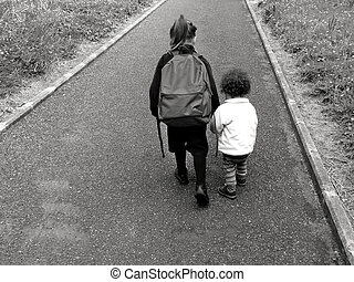 Young sister walks with her older sister to school - Young...