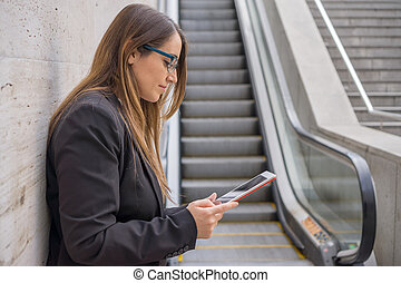 Office woman working with tablet near escalator - Closeup...