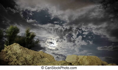 Night and the Moon above the clouds, rocks and underbrush