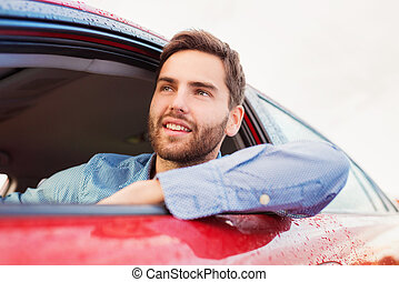 Man driving a car - Handsome young man in a blue shirt...