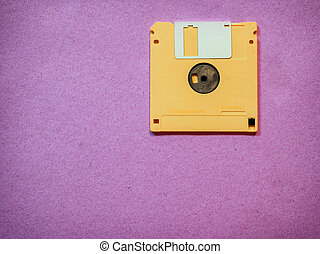 Vintage yellow floppy disk on Magenta background