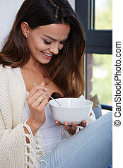 Young woman eating soup - Young woman eating soup by the...