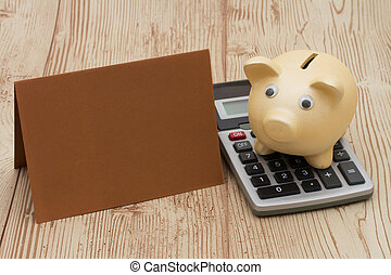 A golden piggy bank with card and calculator on wood background