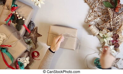 Top view woman wrapping christmas presents With Brown Paper...