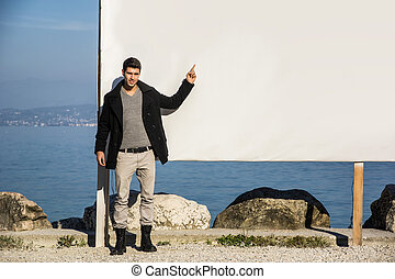 Young man standing next to large blank white billboard, display