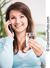 Girl talking on the phone and drinking water