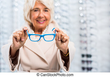 Holding glasses with blue frame - Senior woman holding...